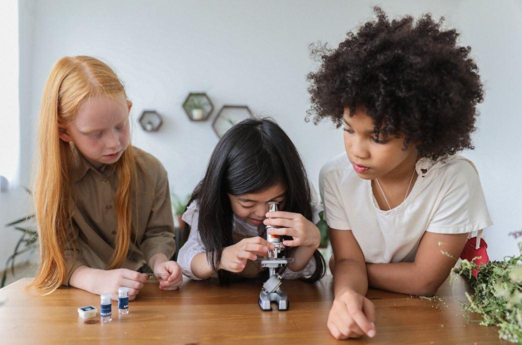 Kinder experimentieren mit einem Mikroskop